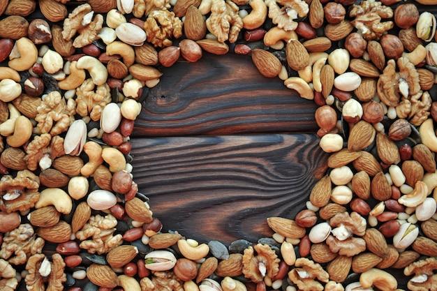 Sfondo di noci diversi assortiti sulla superficie in legno. vista dall'alto