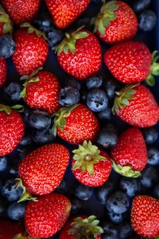 Sfondo di bacche fresche assortite di fragole succose rosse e mirtilli blu di close-up. vista dall'alto.