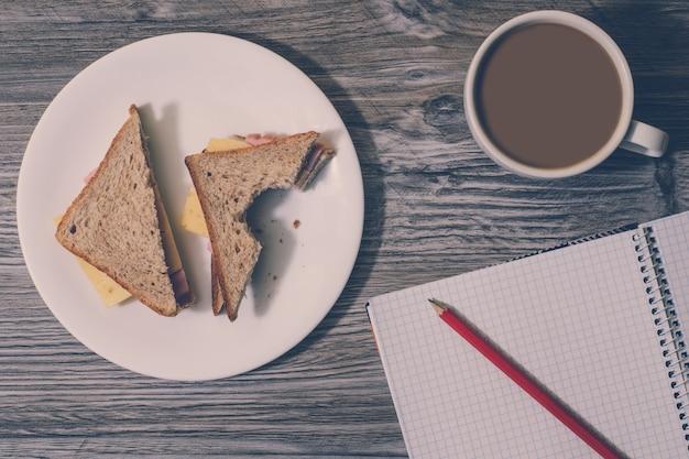 Sfondo di panino al formaggio morso su un piatto rotondo bianco, tazza di caffè caldo, quaderno aperto con una matita su di esso. vista dall'alto.