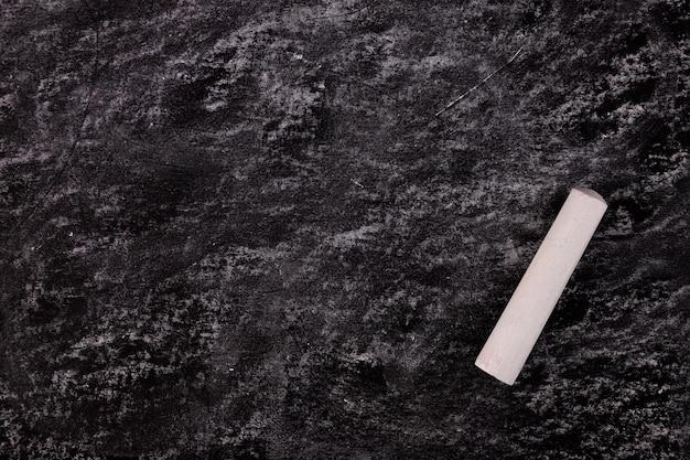 Sfondo di un bordo nero con un unico pezzo di gesso