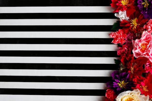 Sfondo di strisce bianche e nere e grandi fiori luminosi bright