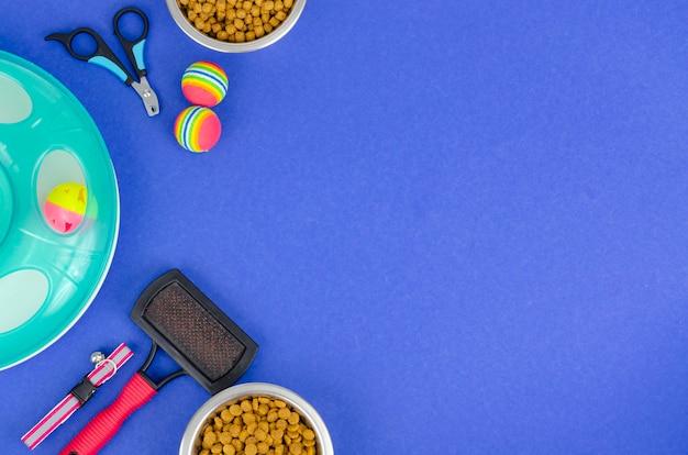 Sfondo di ciotole con cibo, giocattoli e articoli per la cura degli animali domestici, vista dall'alto. foto di studio