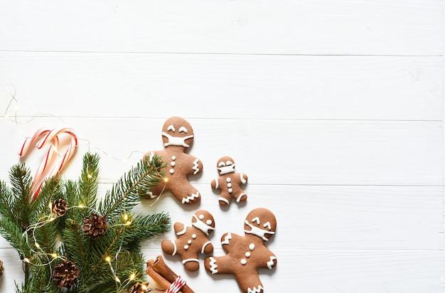 Sfondo a natale. decorazione con abete e pan di zenzero su fondo di legno bianco.