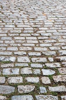 Sfondo: primo piano della vecchia pavimentazione in pietra presso il cortile del mercato all'ingrosso. città di san paolo, brasile