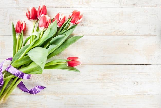 Sfondo per congratulazioni, biglietti di auguri. i tulipani freschi della molla fiorisce, sullo spazio di legno bianco della copia di vista superiore del fondo
