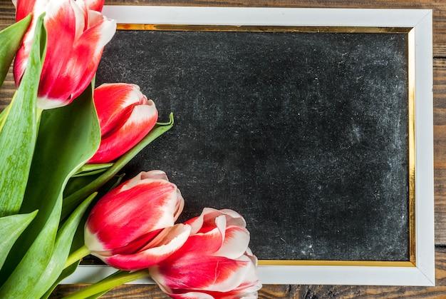 Sfondo per biglietti di auguri congratulazioni fiori di tulipani freschi di primavera con lavagna per il testo su uno sfondo di legno
