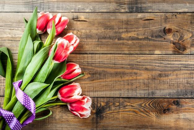 Sfondo per congratulazioni, biglietti di auguri. i tulipani freschi della molla fiorisce, su uno spazio di legno della copia di vista superiore del fondo