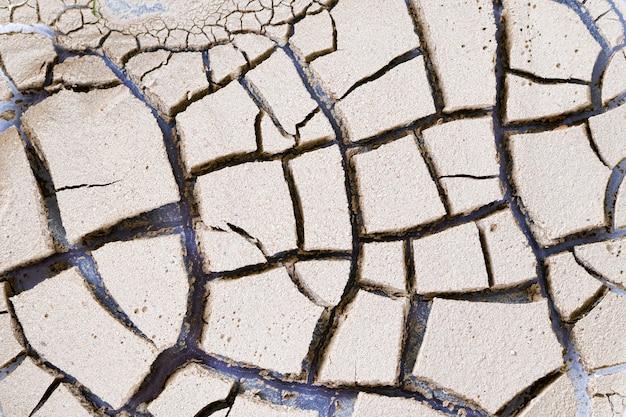 Primo piano di argilla incrinato sfondo. terra secca