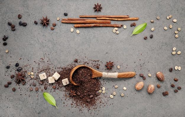 Sfondo di chicchi di caffè tostati scuri e polvere di caffè con installazione di palette su cemento scuro.