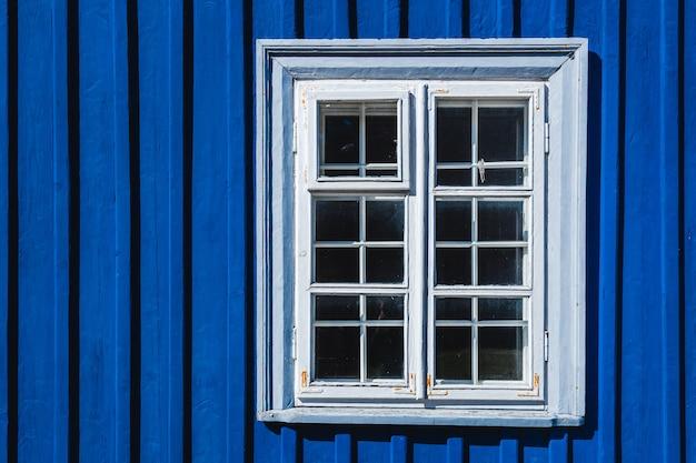 Sullo sfondo di una parete di colore blu intenso con finestra