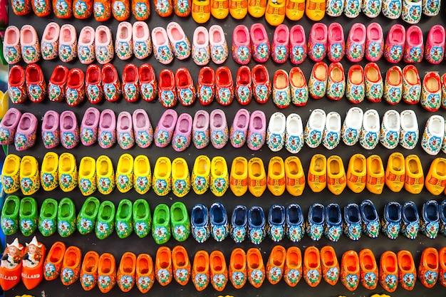 Sfondo di diversi colori zoccoli di legno - souvenir magnete, scarpe olandesi tradizionali