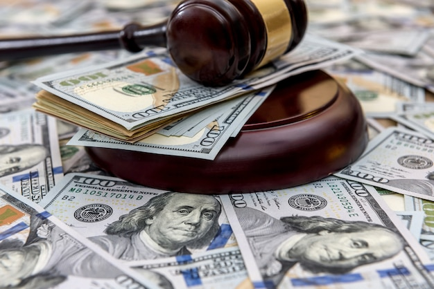 Sullo sfondo di dollari ci sono dollari e su di loro si trova il martello del giudice da vicino