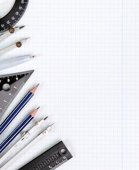 Sfondo: strumenti di disegno su un foglio di quaderno bianco nella scatola