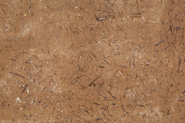 Sfondo di argilla secca e screpolata con trucioli di legno