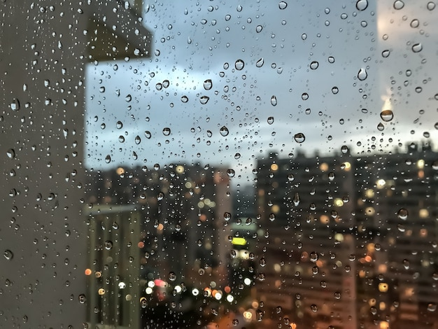 Gocce d'acqua di sfondo. goccia di pioggia sui vetri delle finestre. modello naturale di gocce di pioggia. colpo astratto di gocce di pioggia sul vetro. città di notte e balcone fuori dalla finestra. messa a fuoco selettiva. spazio per testo o logo