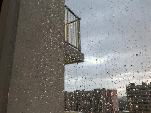Sfondo gocce d'acqua. goccia di pioggia sui vetri delle finestre. modello naturale di gocce di pioggia. colpo astratto di gocce di pioggia sul vetro. città di notte e balcone fuori dalla finestra. messa a fuoco selettiva. spazio per testo o logo