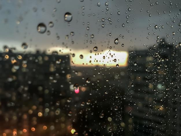 Gocce d'acqua di sfondo. goccia di pioggia sui vetri delle finestre. modello naturale di gocce di pioggia. colpo astratto di gocce di pioggia sul vetro. città di notte e tramonto fuori dalla finestra. messa a fuoco selettiva. spazio per testo o logo