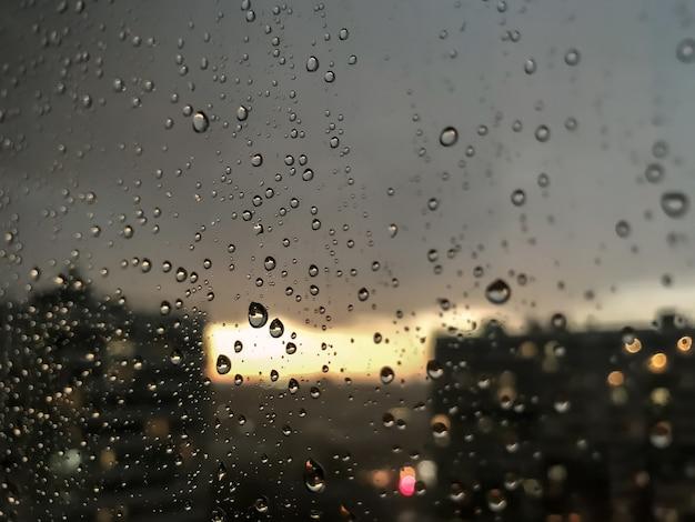 Sfondo gocce d'acqua. goccia di pioggia sui vetri delle finestre. modello naturale di gocce di pioggia. colpo astratto di gocce di pioggia sul vetro. città di notte e tramonto fuori dalla finestra. messa a fuoco selettiva. spazio per testo o logo
