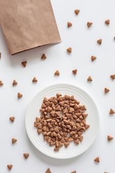 Sfondo di cibo per gatti secco e imballaggi di carta. prenditi cura dei gatti domestici.