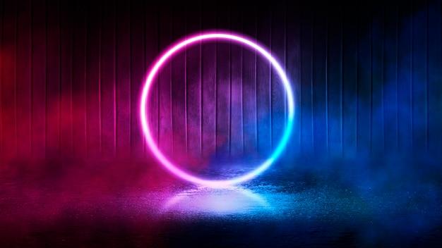 Sfondo del palco vuoto, stanza. riflessione su pavimentazione bagnata, cemento. luci sfocate al neon. cerchio al neon figura al centro, fumo