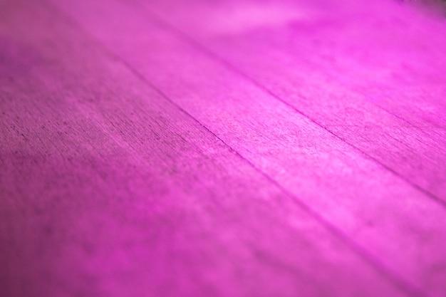 Sfondo di un tavolo di legno vuoto, sfondo viola astratto con bagliore al neon. avvicinamento.
