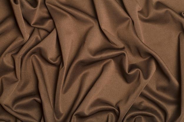 Tessuto di fondo. tessuto tessile marrone con texture