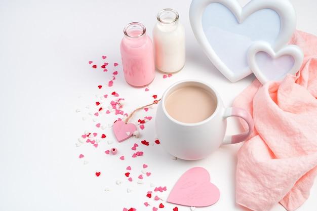 Sfondo per il 14 febbraio con una tazza di caffè con latte, una cornice a forma di cuore e una bottiglia di latte