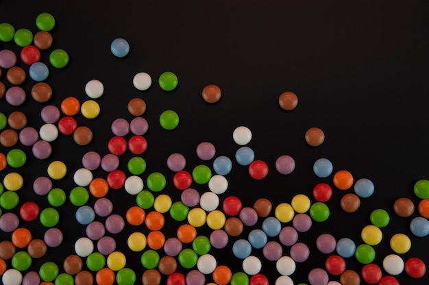 Sfondo sotto forma di caramelle colorate spruzzate su uno sfondo nero