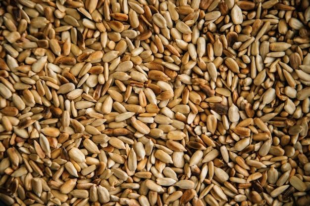 Sfondo di semi di girasole sbucciati fritti. la consistenza dei piccoli grani. raccolto di semi. cibo salutare.