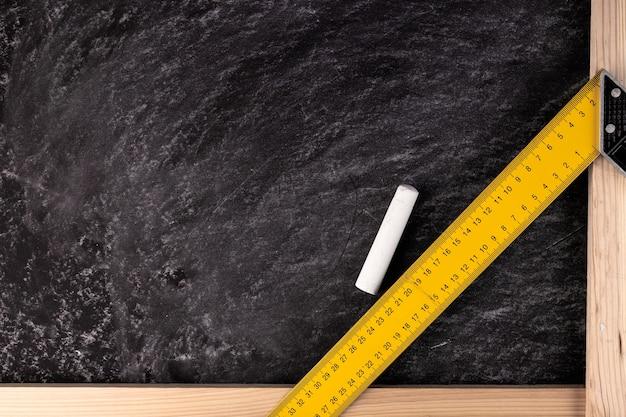 Sfondo da un bordo nero con un pezzo di gesso e un righello