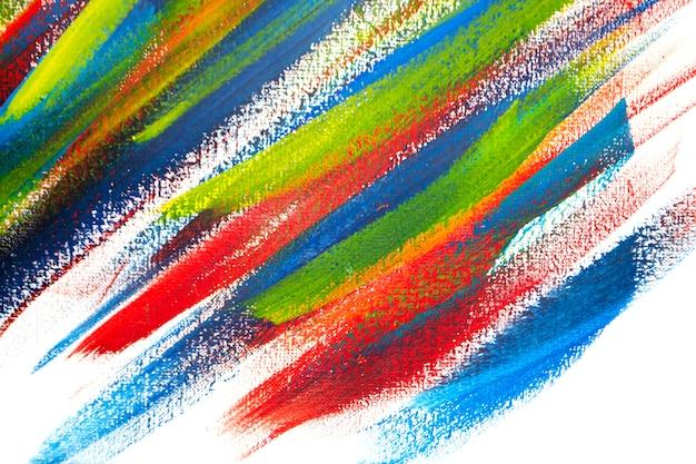 Sfondo da diversi tratti di vernice rossa, gialla, verde e blu con pennello sul primo piano sfondo bianco. sfondo colorato luminoso di linee di pennello. mescolando strisce di colore di vernice su tela bianca