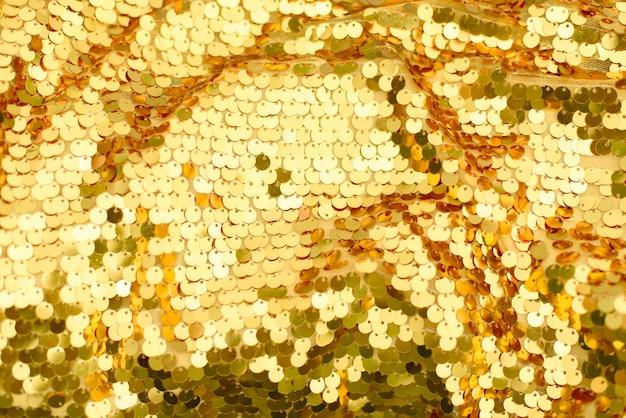 Sfondo da paillettes squame dorate. astratto scintillante