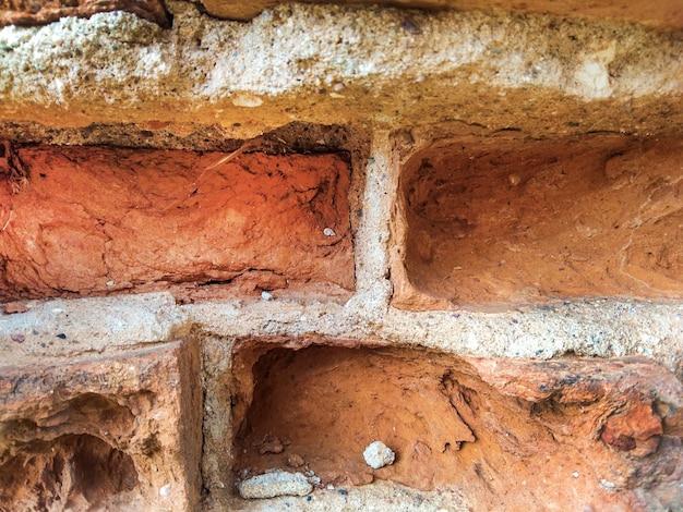 Sfondo di mattoni rossi-marroni cavi, vecchi e grezzi