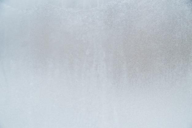 Sfondo di vetro gelido ricoperto di brina e neve, inverno, struttura del ghiaccio