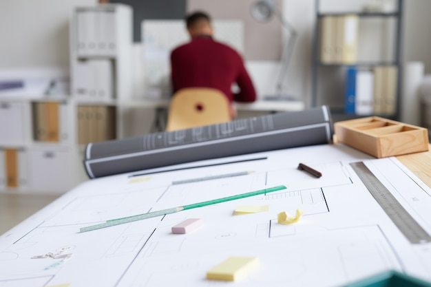 Immagine di sfondo di architetti sul posto di lavoro con blueprint e strumenti sul tavolo da disegno in primo piano,