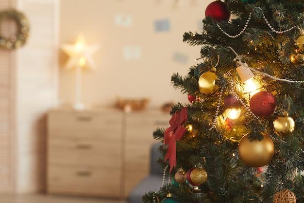 Immagine di sfondo del bellissimo albero di natale decorato con baulbs dorati in interni accoglienti, copia dello spazio