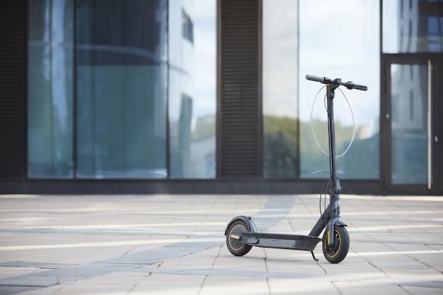 Immagine di sfondo del nero scooter elettrico in piedi sul pavimento piastrellato contro la costruzione di vetro nel contesto urbano, copia dello spazio