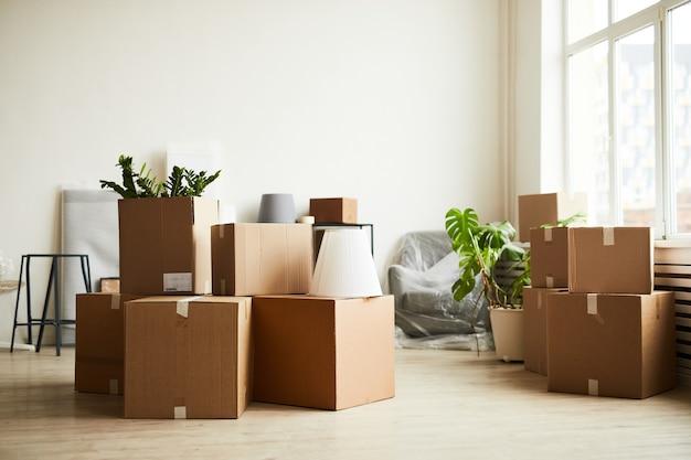 Immagine di sfondo di scatole di cartone nella stanza vuota che si spostano in un nuovo spazio di copia del concetto di casa