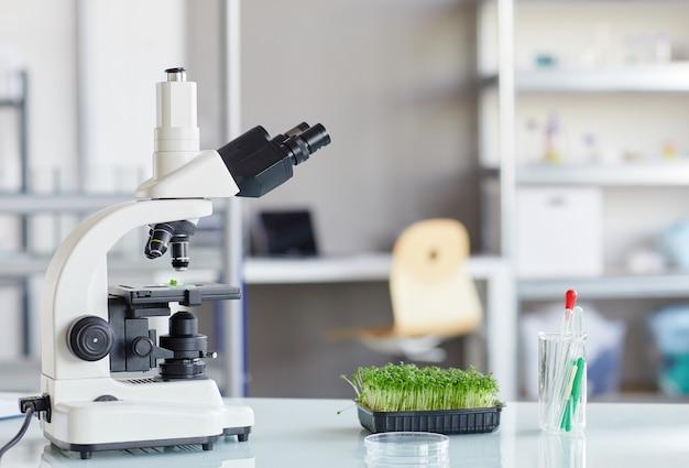 Immagine di sfondo del microscopio elettronico e degli alberelli di piante sul tavolo dell'apparecchiatura nel laboratorio di biotecnologia, copia dello spazio
