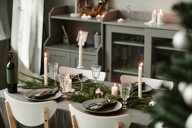 Immagine di sfondo di un elegante tavolo da pranzo decorato per natale in toni minimi di grigio e argento co...