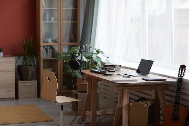 Immagine di sfondo di un invitante studio di registrazione a casa con apparecchiature musicali e chitarra, spazio di copia