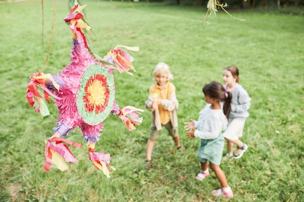 Immagine di sfondo di una pinata rosa alla festa di compleanno con un gruppo eterogeneo di bambini che giocano all'aperto copia s...