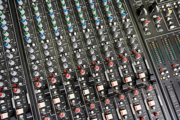 Immagine di sfondo delle manopole del fader e dei canali ssl raffinati sul bordo di registrazione nero nello studio di musica