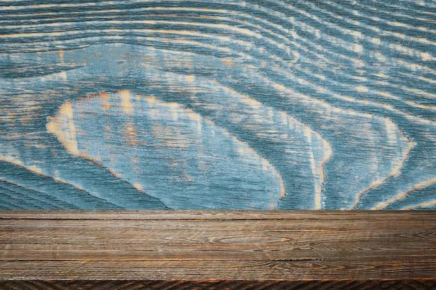 Lo sfondo è costituito da tavole di legno vuote e una parete strutturata con illuminazione e vignettatura. per dimostrazioni di prodotti, spazio libero, layout, mockup, tabellone prospettico, tabellone di sfondo.