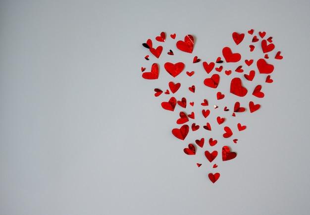 Sfondo di molti piccoli cuori rossi che formano un grande cuore isolato su uno sfondo bianco
