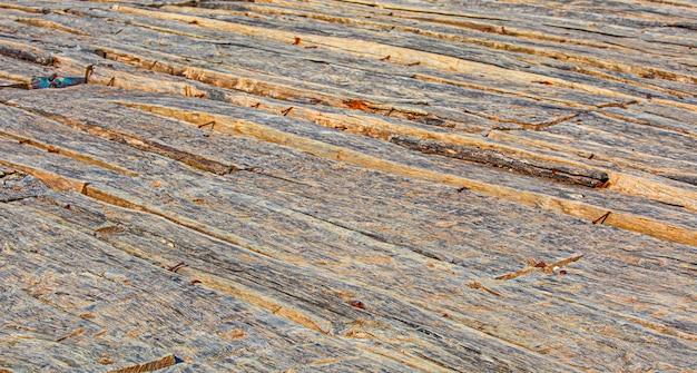 Sfondo di una vecchia stanza in legno naturale con una trama del pavimento disordinata e sgangherata all'interno di un vuoto trascurato