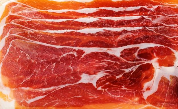 Sfondo di trama di jamon di carne rosa di carne di maiale affumicata. vista dall'alto.