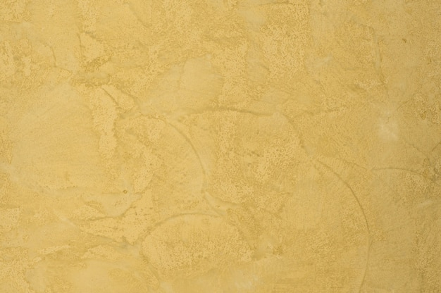 Fondo della trama intonacata con effetto marmo color oro. sfondo artistico fatto a mano