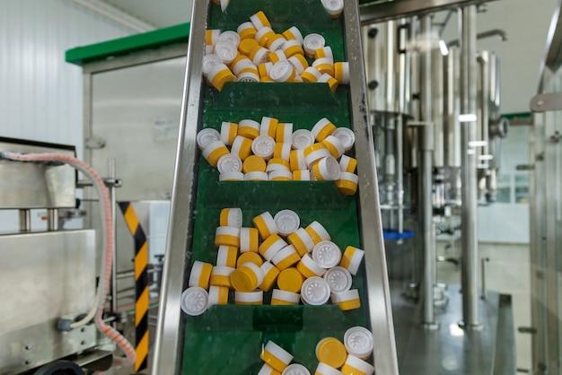Sfondo di tappi di bottiglia di plastica. tappi di plastica per bottiglie di giallo e bianco. il processo produttivo è una linea per il confezionamento di bottiglie di plastica.
