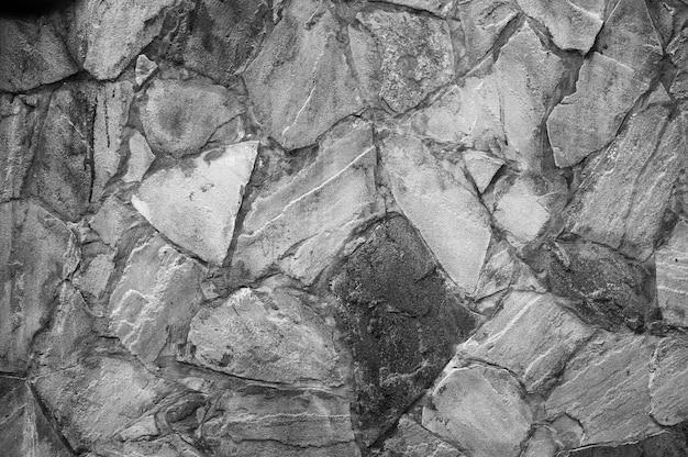 Sullo sfondo di un muro di pietra texture. muro grigio bianco e nero